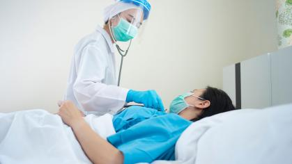 Doctor uses a stethoscope to check on patient in bed
