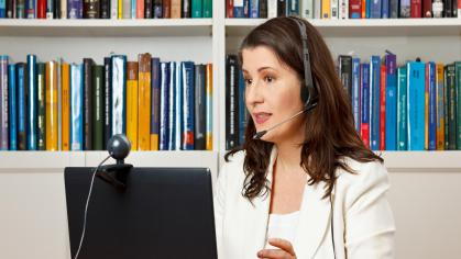 woman speaking on headset sitting at computer