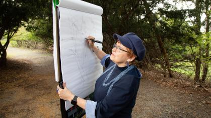 Student draws on canvas outdoors